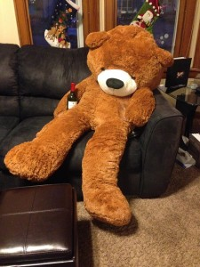 Giant Teddy Bear sitting on couch drinking wine