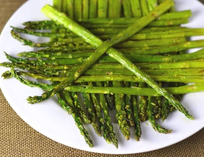 Close up look at roasted asparagus on a plate.