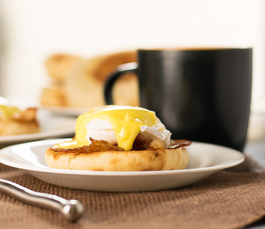 Close up look at Bacon and Eggs Benedict served with a fork.
