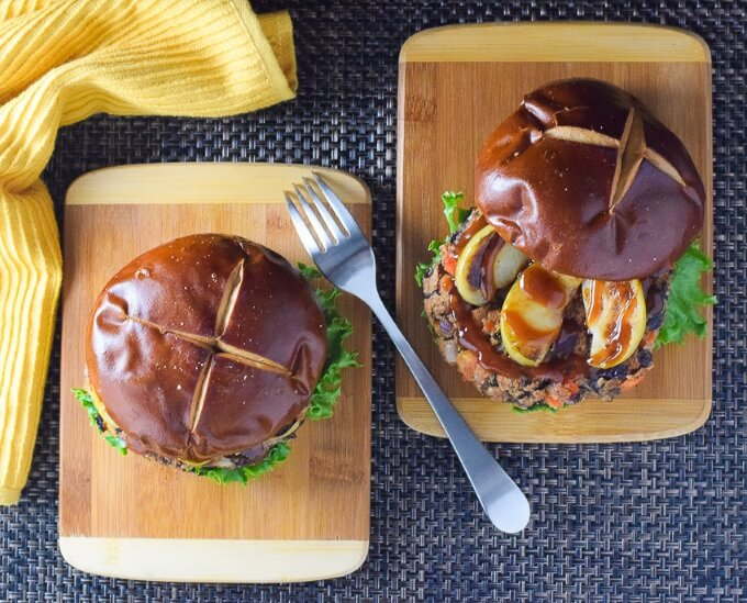 Two black bean burgers topped with pretzel buns shown from above.