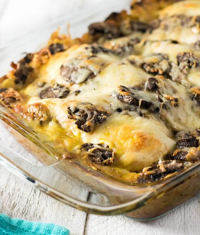 Hot pan with baked chicken covered by portobello mushrooms and melted swiss cheese