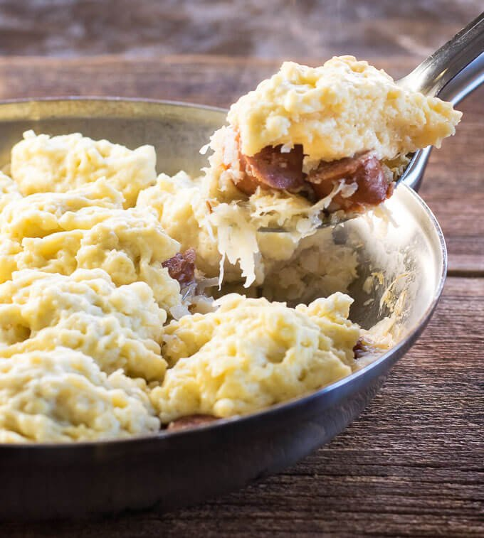 Sauerkraut and Dumplings with Kielbasa being scooped from skillet