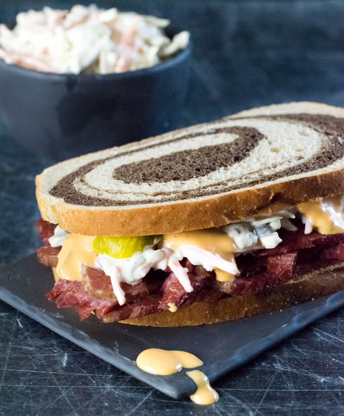 Corned beef sandwich on rye with pickles and coleslaw