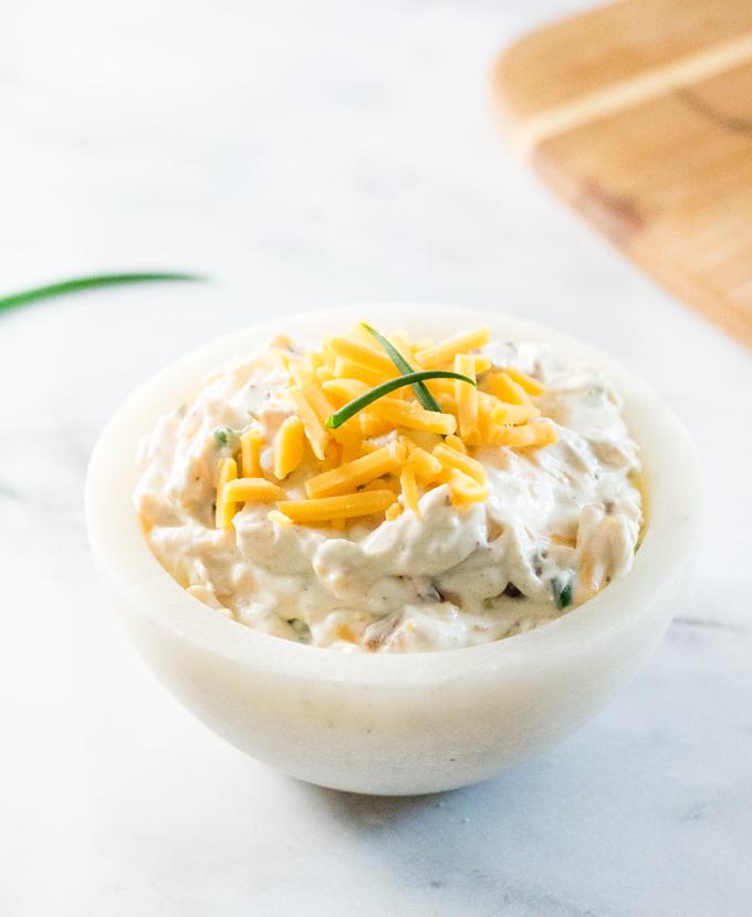 Loaded baked potato dip in white bowl