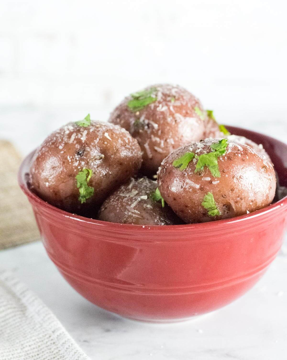 Boiled red potatoes in red bowl with Parmesan sprinkled on top.