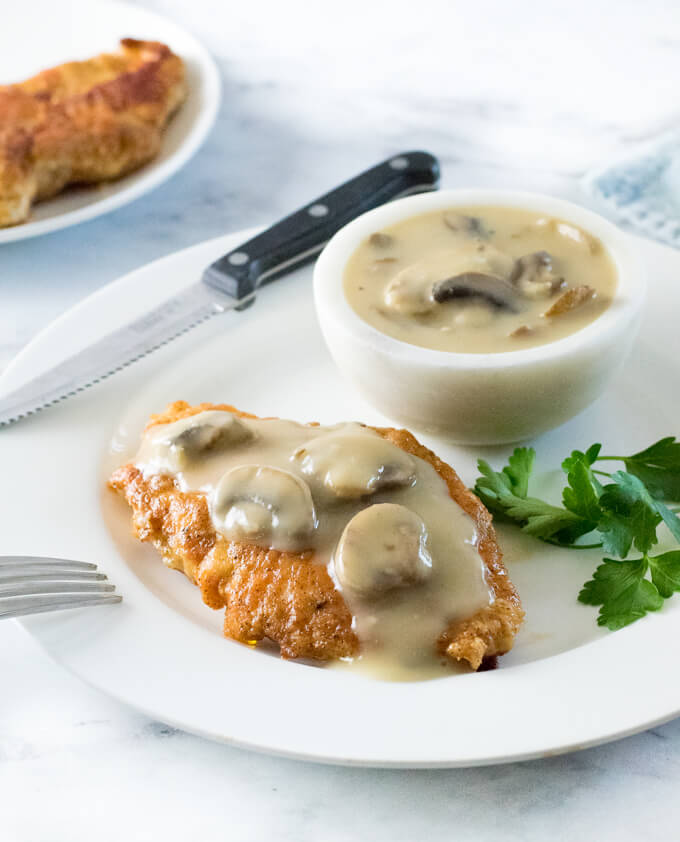 Chicken with mushroom gravy on a white plate with knife.