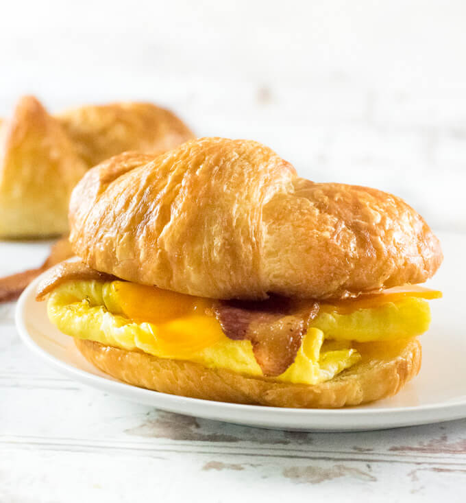 Croissant Breakfast Sandwich shown close up with white background.