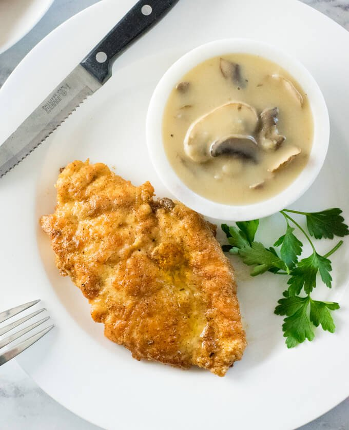 Lightly breaded chicken next to bowl of mushroom gravy.