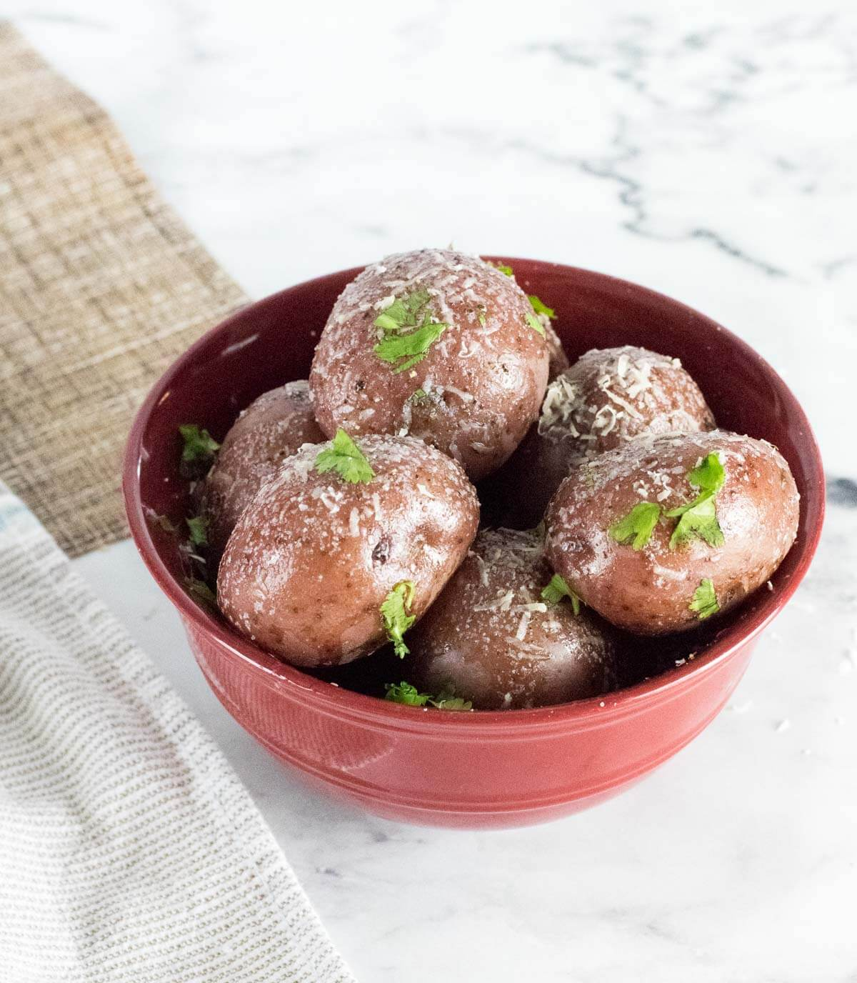 Red potatoes with butter and Parmesan in a bowl with white background.