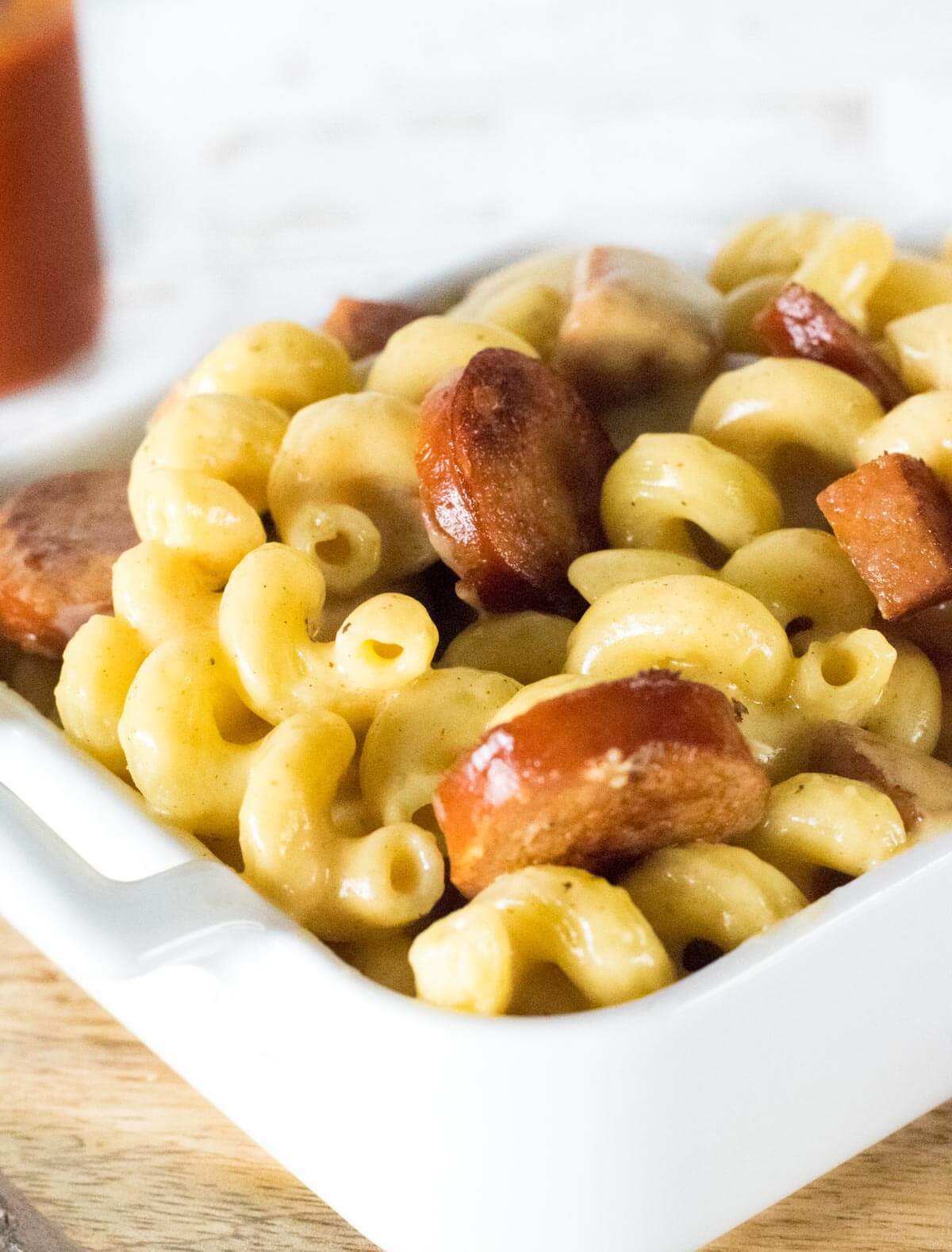 Mac and cheese with andouille sausage in a white dish.
