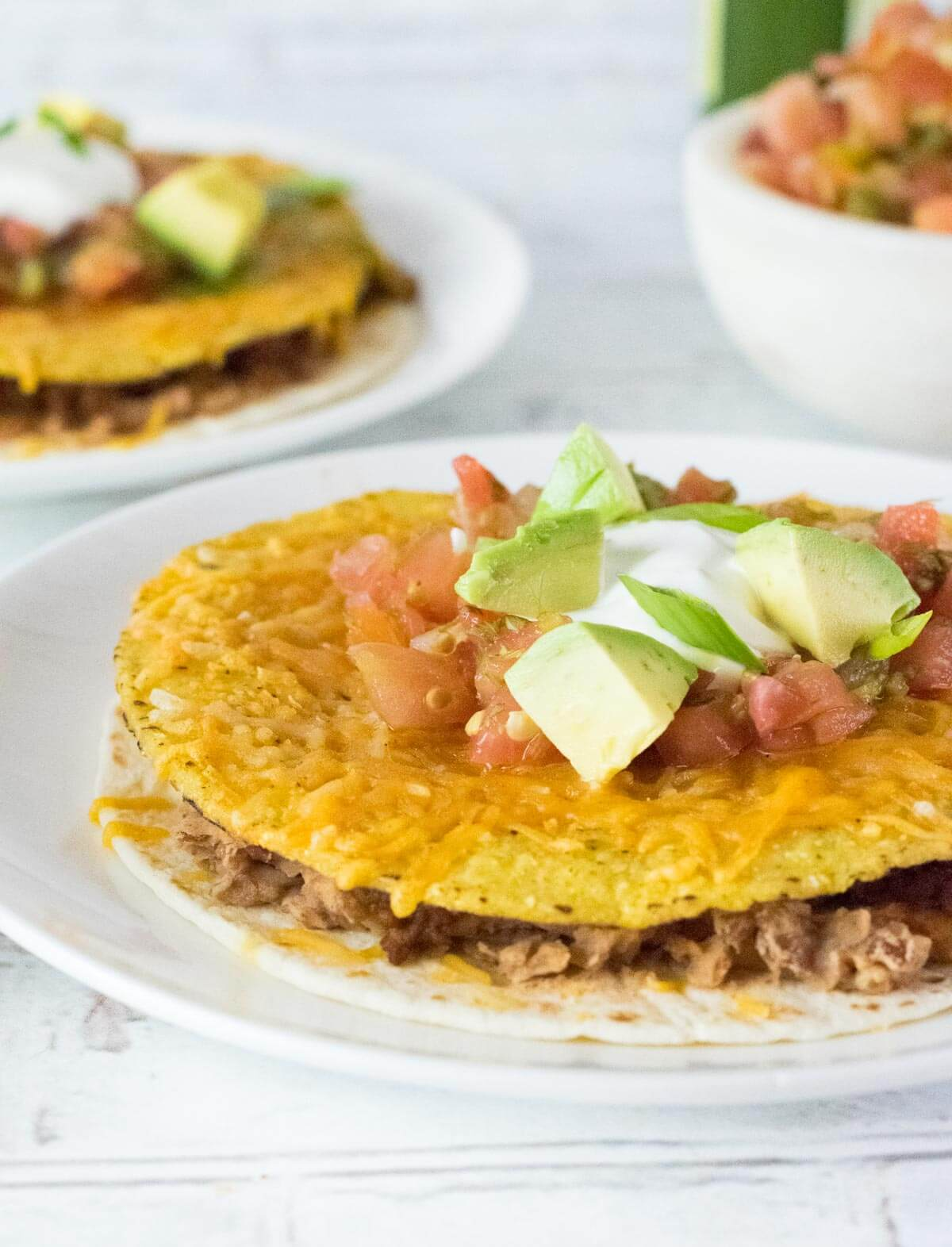Mexican pizza toppings shown with avocado, tomato, sour cream.