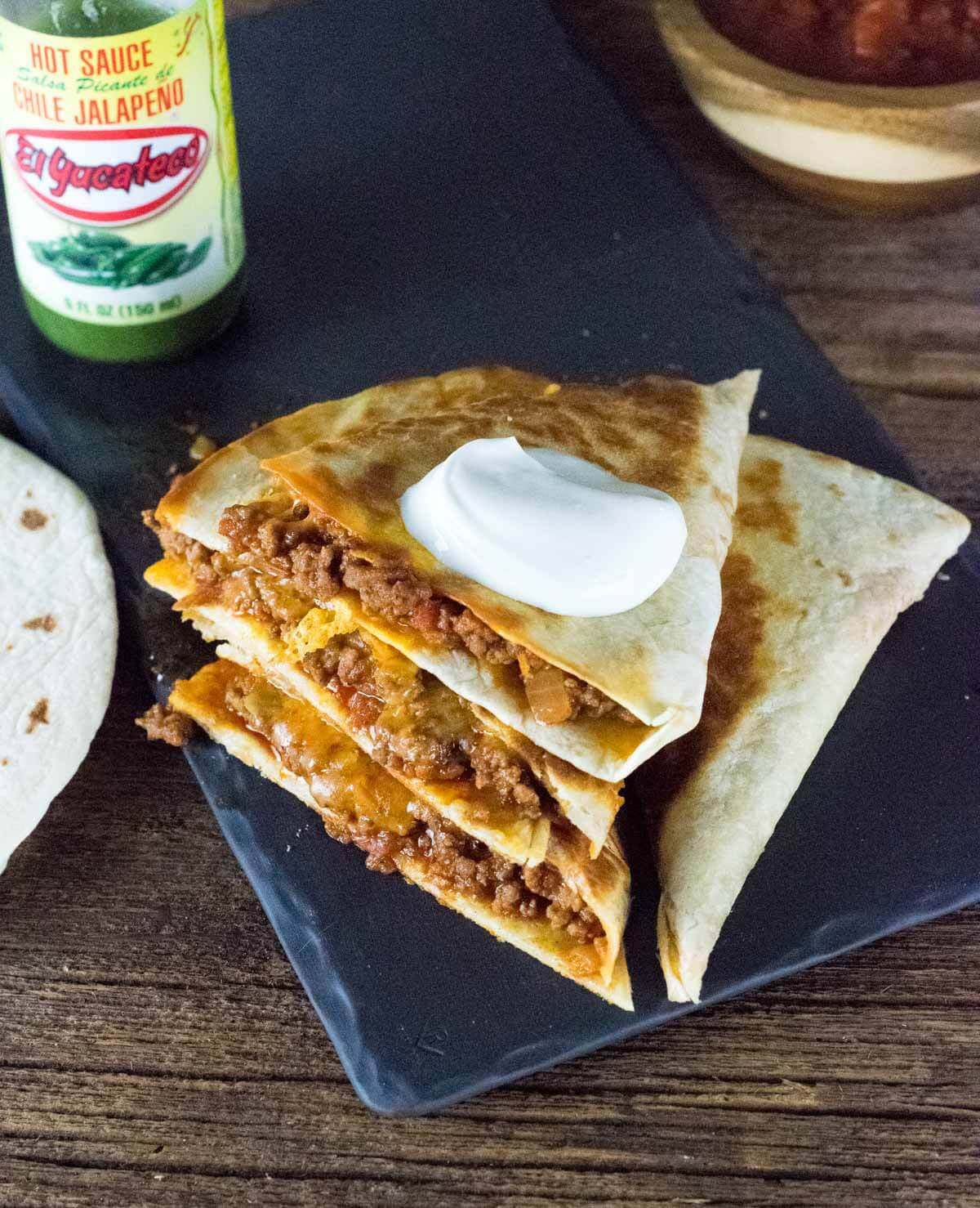 Ground beef quesadillas stacked on top of each other and topped with sour cream.