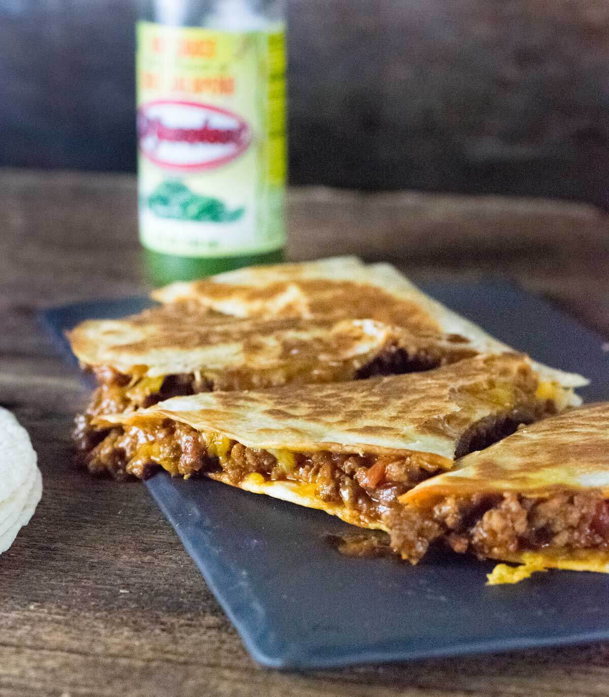 beef quesadillas with cheese dripping out.