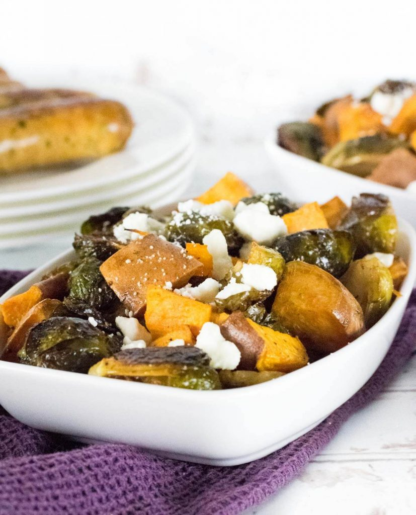 Sweet potatoes and Brussels sprouts topped with feta and served in a white dish.