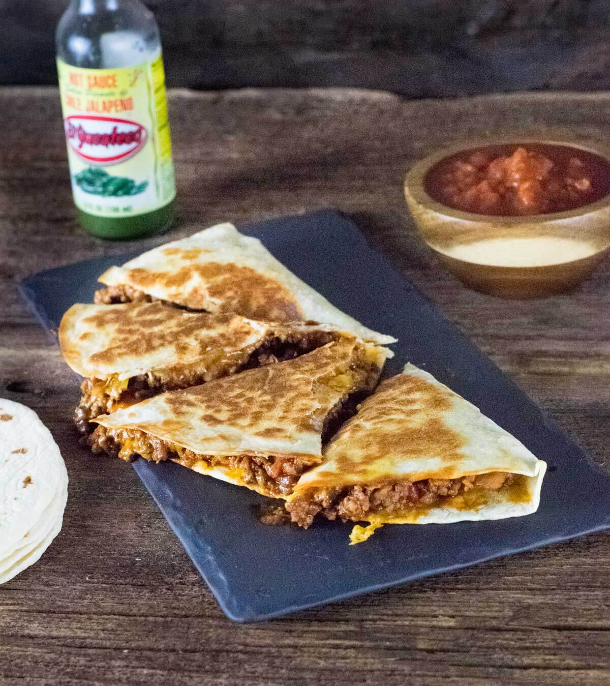 quesadilla on black tray with hot sauce.