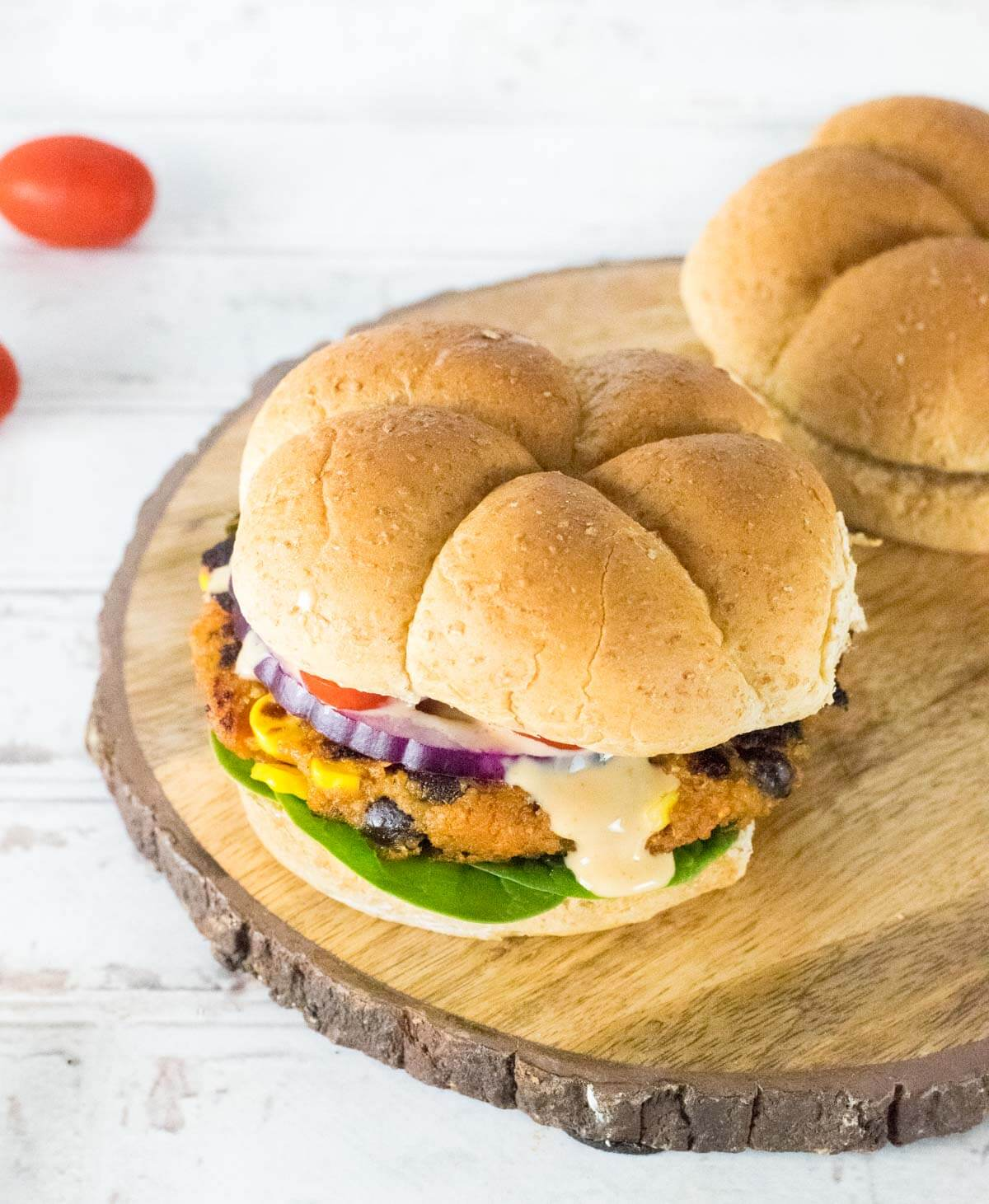 Sweet potato black bean burger toppings and bun with sauce dripping down.