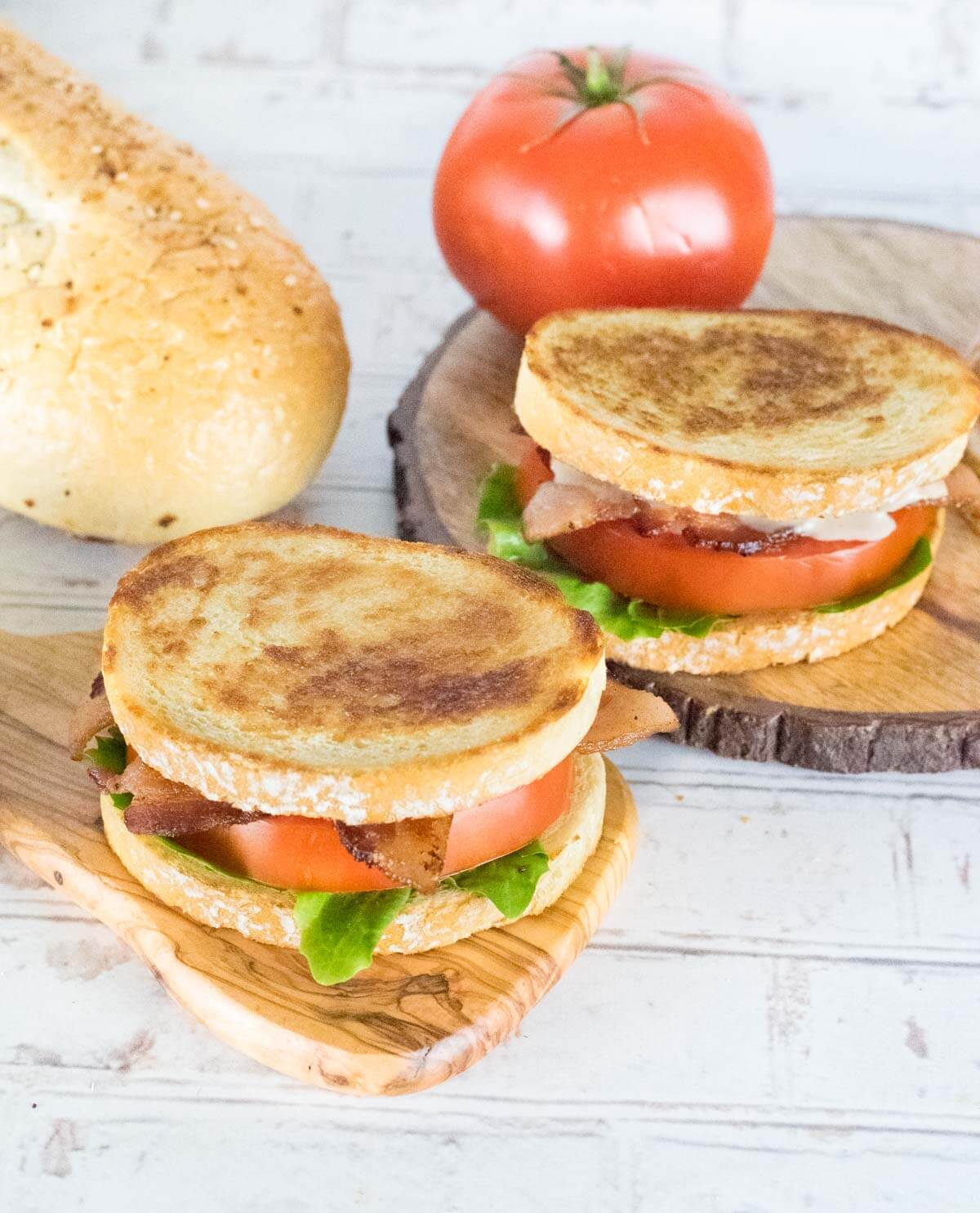Two Gourmet BLTs with fresh bread on wooden trays.