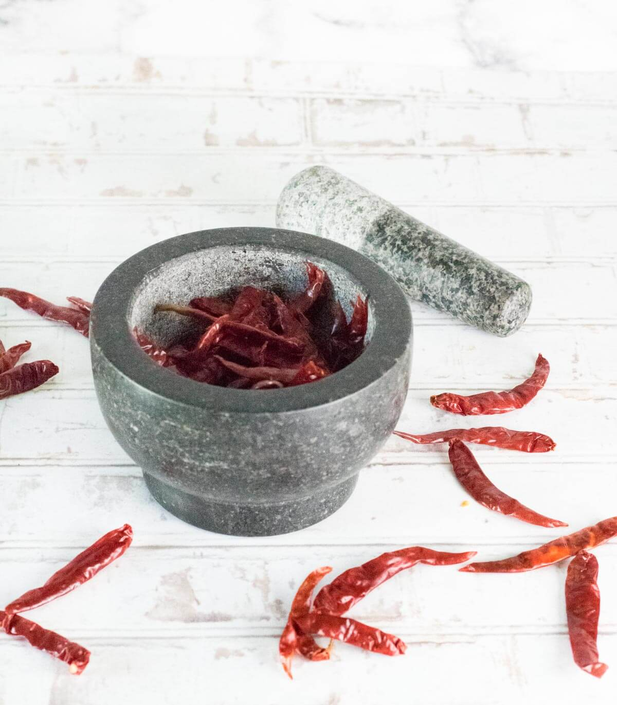 Grinding paprika peppers in mortar and pestle.