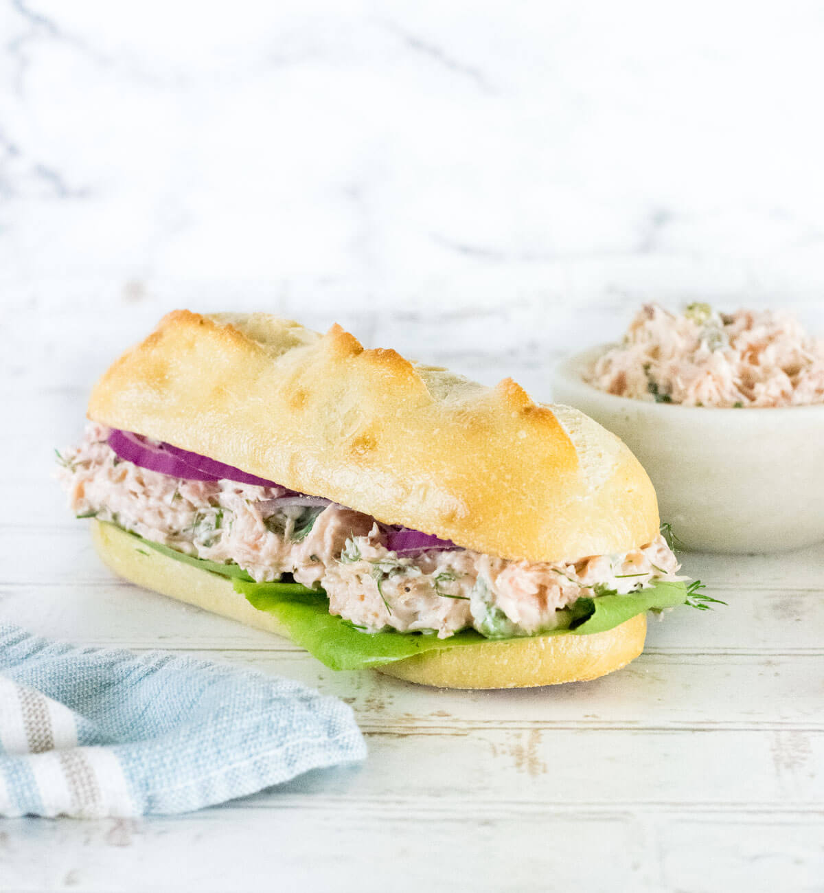 Salmon Salad Sandwich on hoagie roll with lettuce.