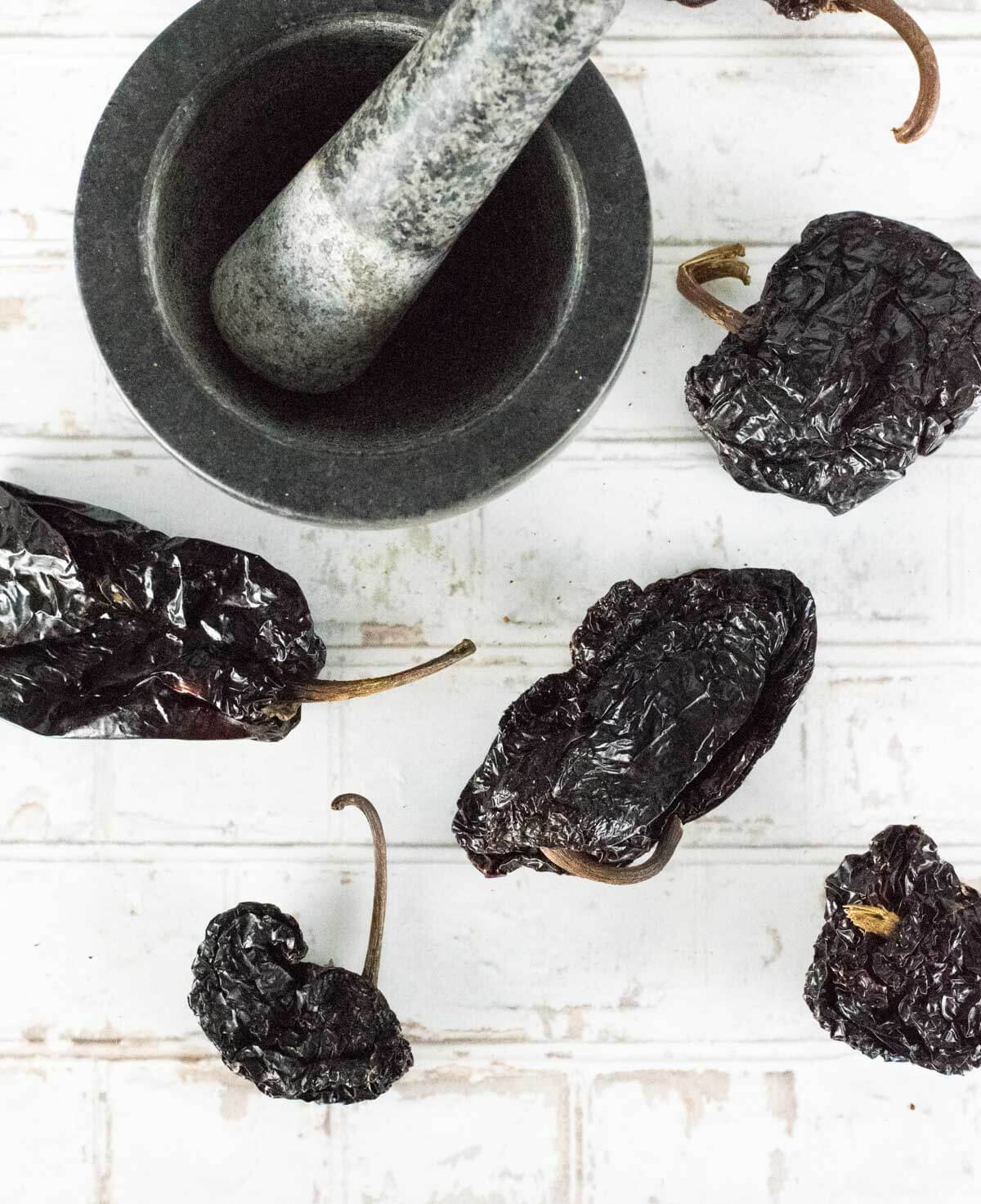 Dried ancho chiles sitting by mortar and pestle.