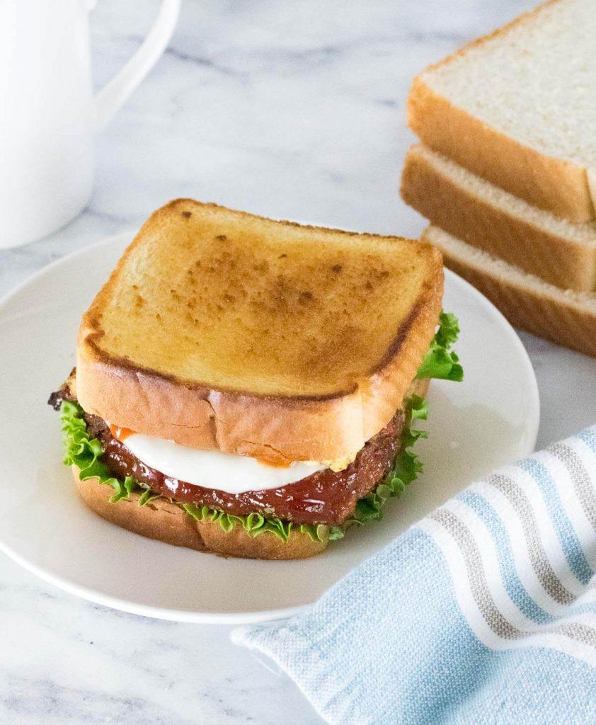 Leftover meatloaf sandwich on white plate.