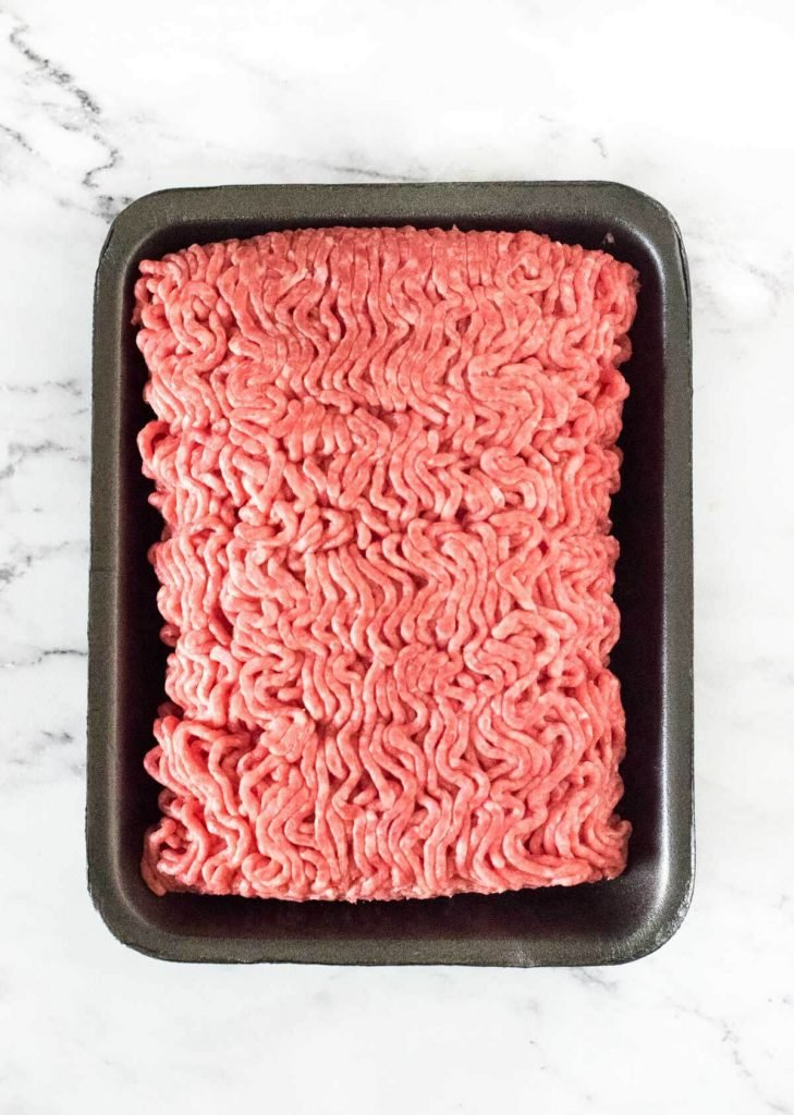 Raw hamburger in black container.