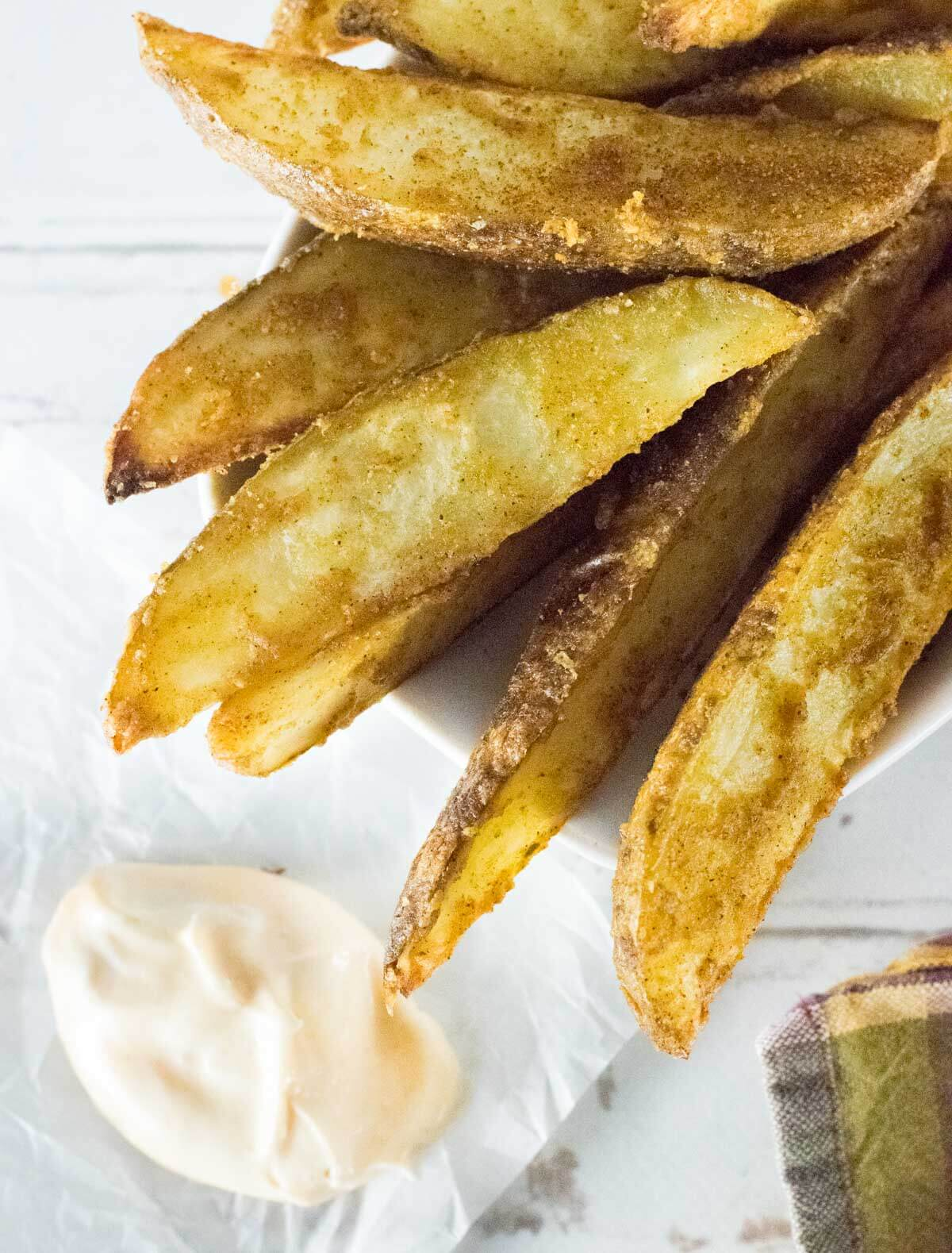 Cajun potato wedges with dipping sauce on wax paper.