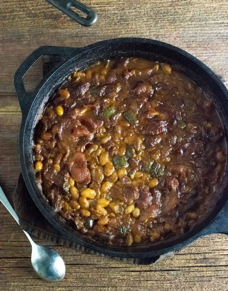 Pot of grilled Baked Beans resting on wooden board.
