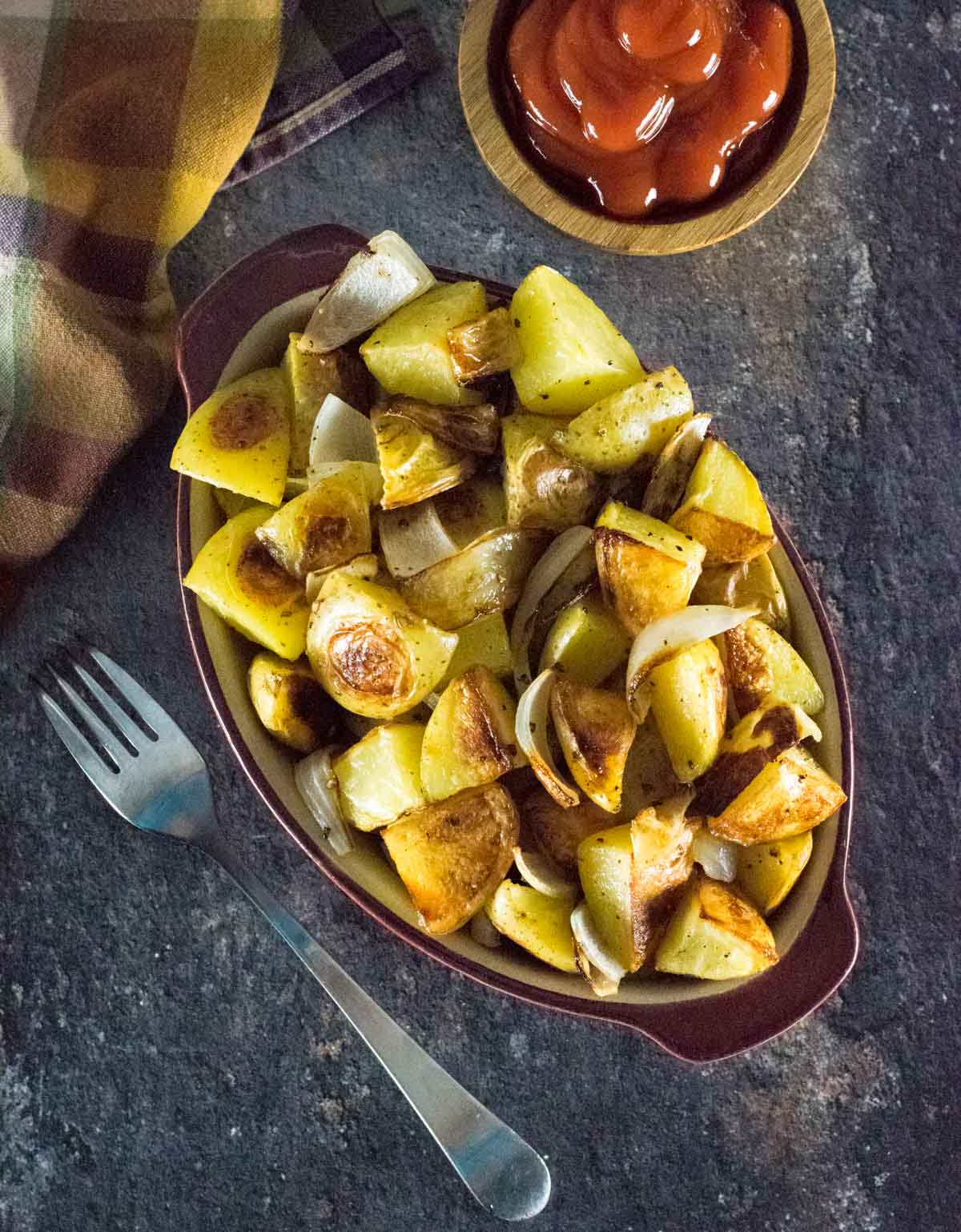 Roasted potatoes and onions shown from above with fork and kitchen towel alongside.