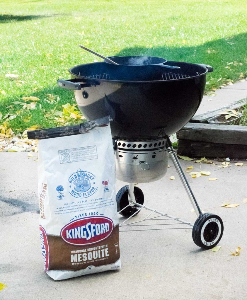Kingsford Mesquite sitting by charcoal grill.