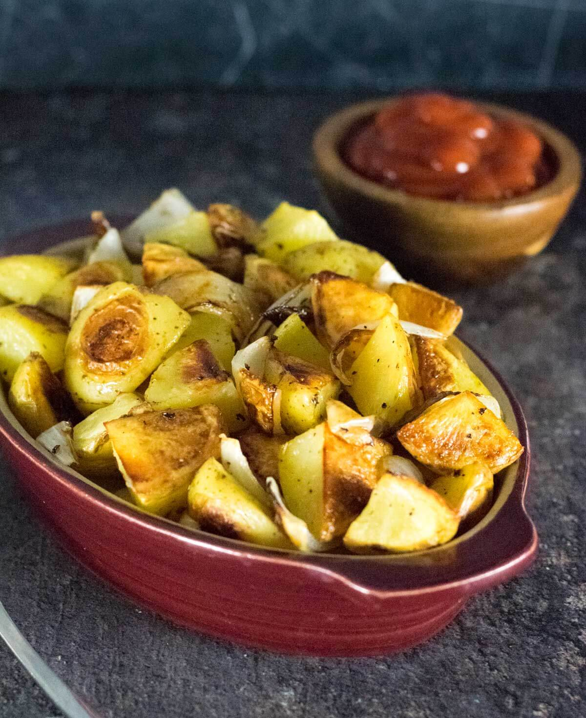 Potatoes and onion with bowl of ketchup.
