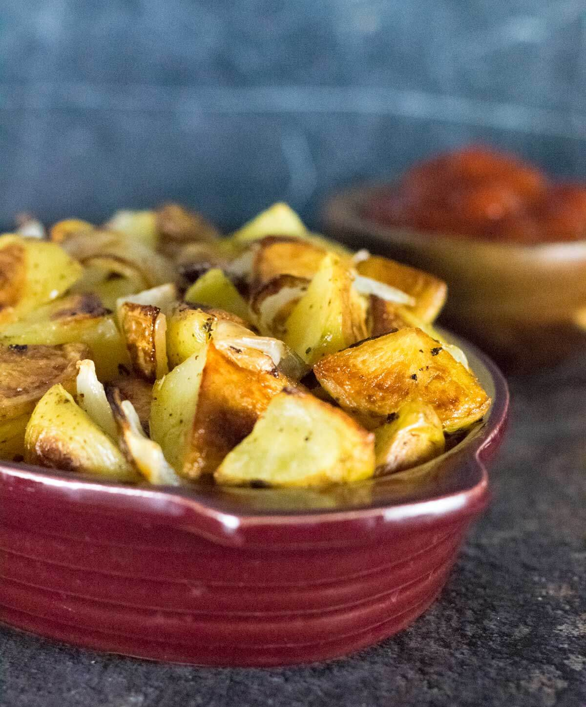 Roasted potatoes and onion in red bowl.