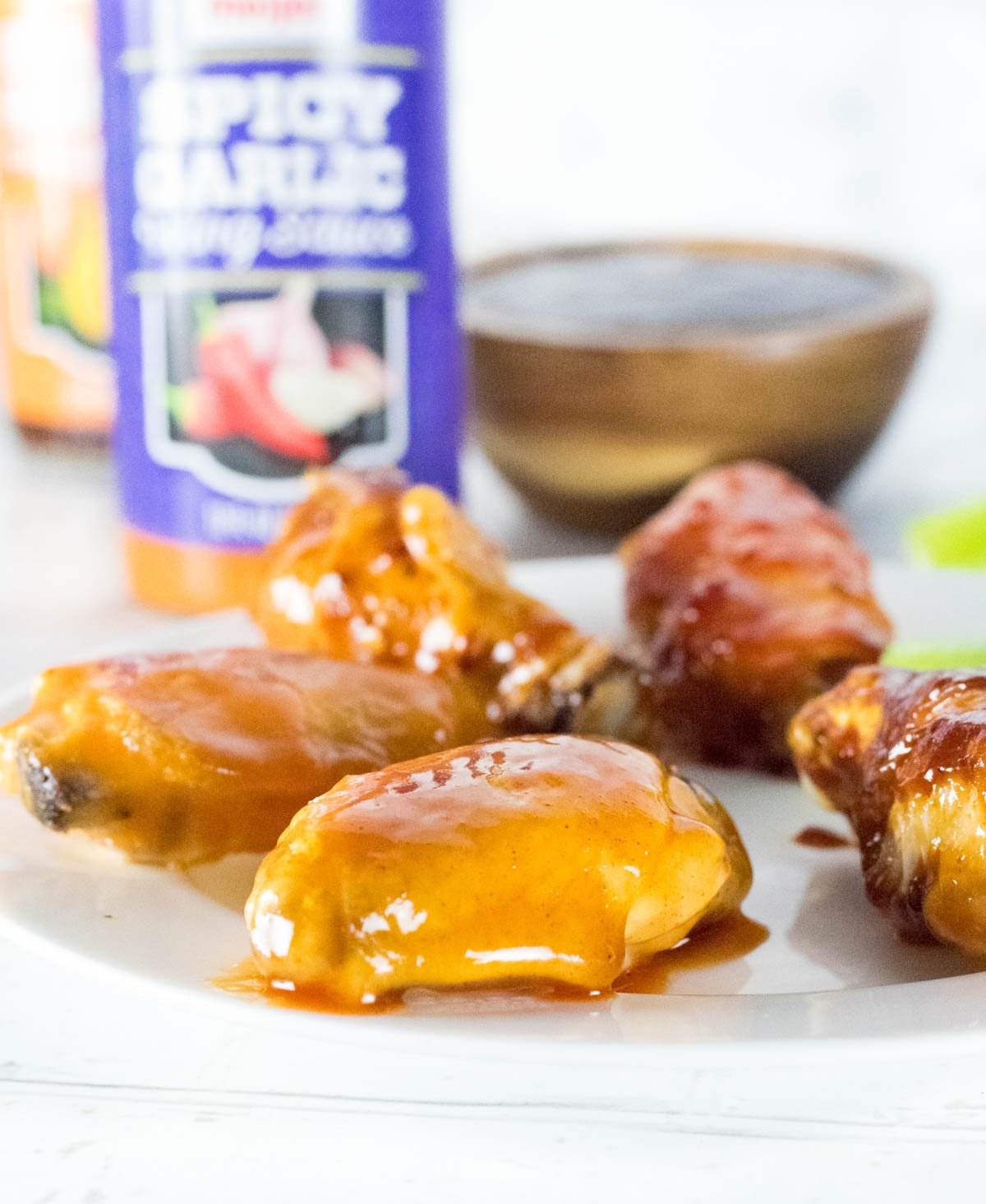 Sauced Chicken Wings with sauce bottle behind.