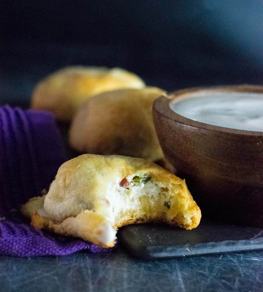 Jalapeno Popper Bites with ranch dressing sitting by purple towel.