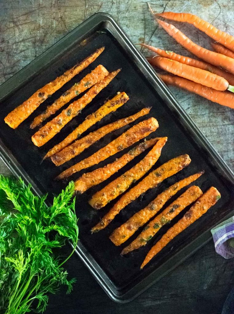 Parmesan Roasted Carrots on brown pan with raw carrots alongside.