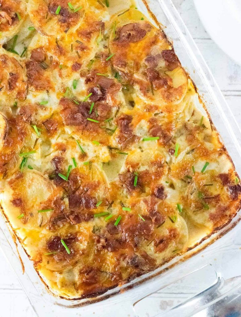 Loaded scalloped potatoes viewed in clear dish from above.
