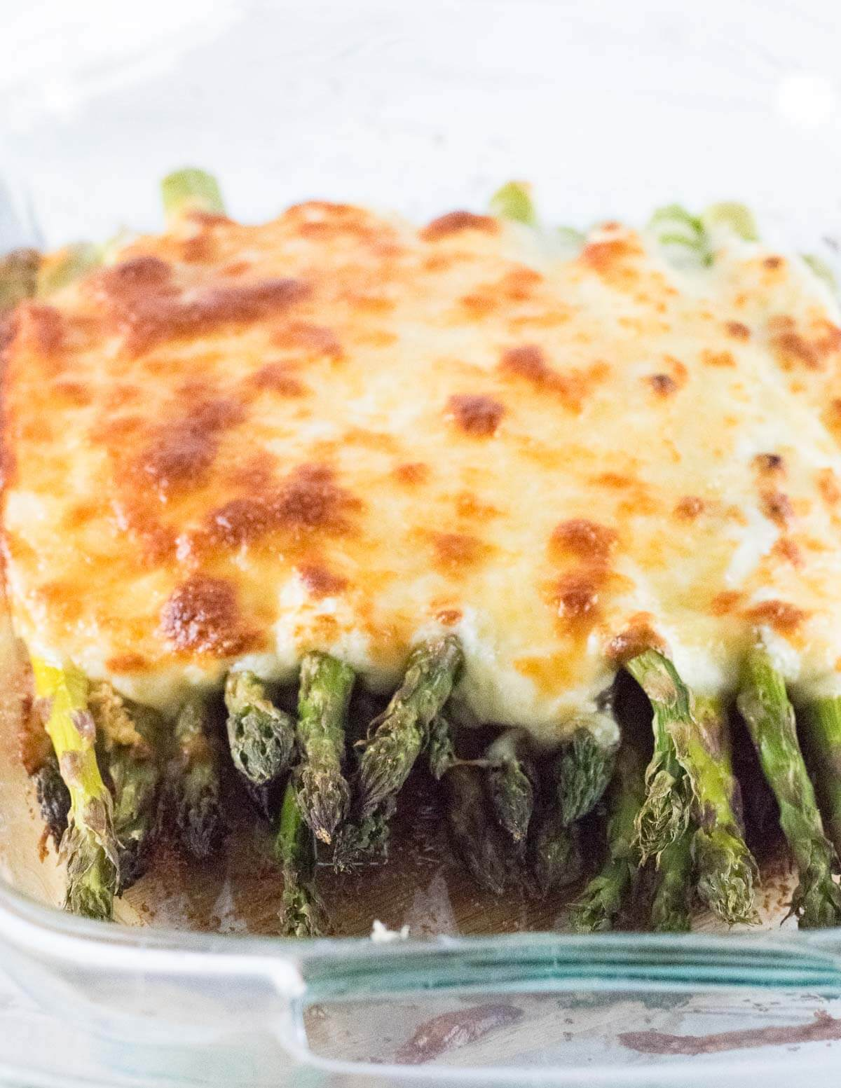 Close up view of baked asparagus with cheese melted on top.