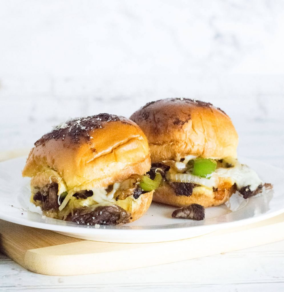 Two Philly cheesesteak sliders on a white plate.