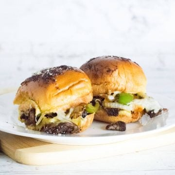 Squared image of two Philly cheesesteak sliders on plate.