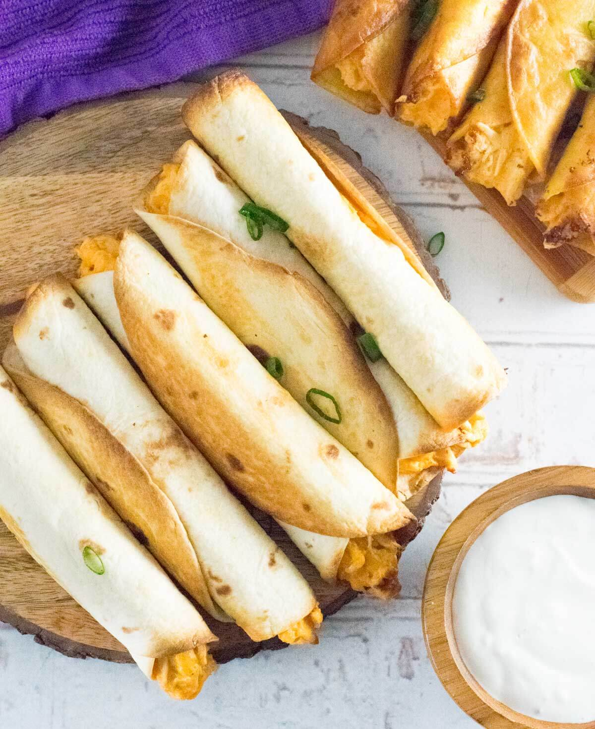 Baked buffalo chicken taquitos on wooden tray shown from above.