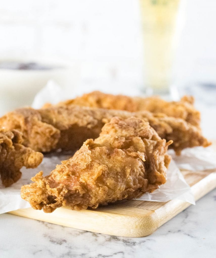 Beer battered chicken tenders on small cutting board.