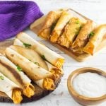 Buffalo chicken taquitos on two platters showing them baked and fried.