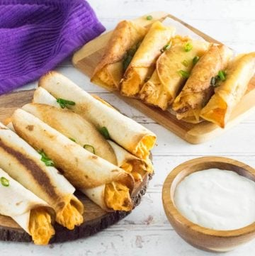 Buffalo chicken taquitos served with dipping sauce on wooden trays.