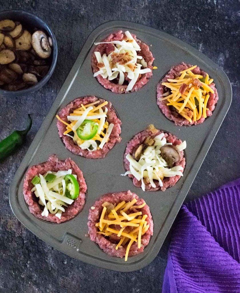 Assembling burger bowls in muffin pan.