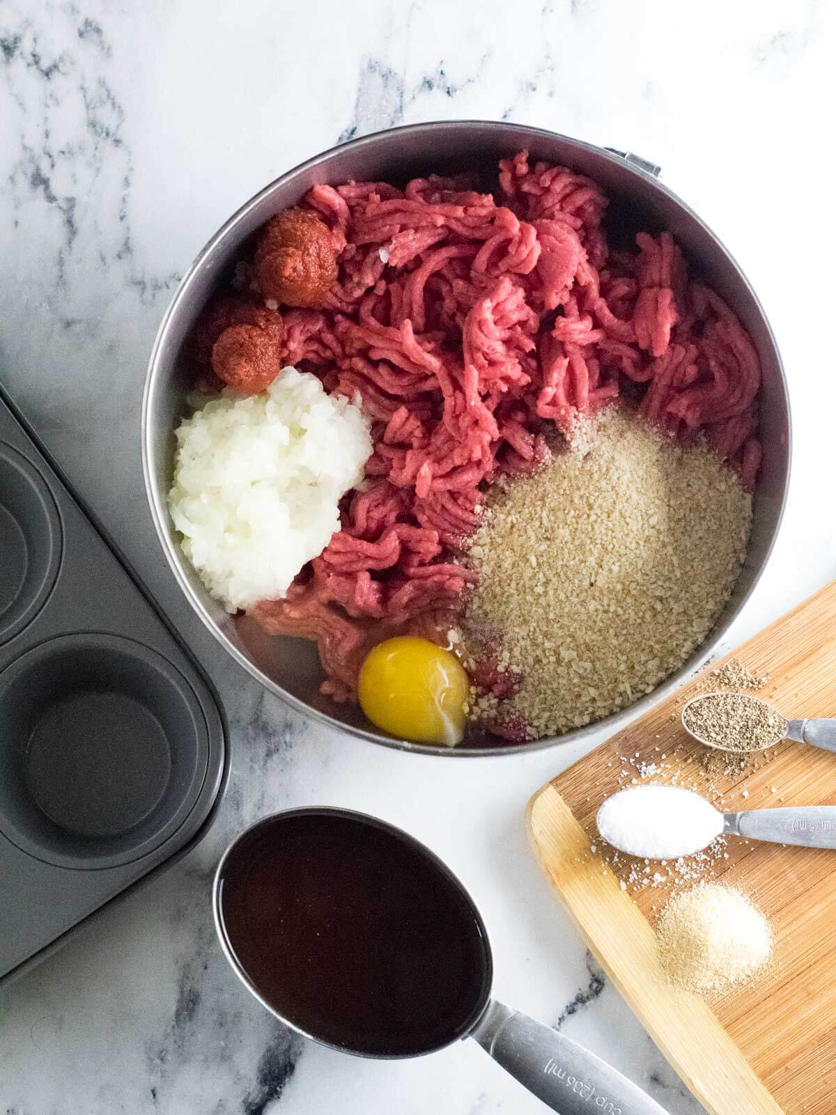 Meatloaf muffin recipe ingredients in a large bowl.