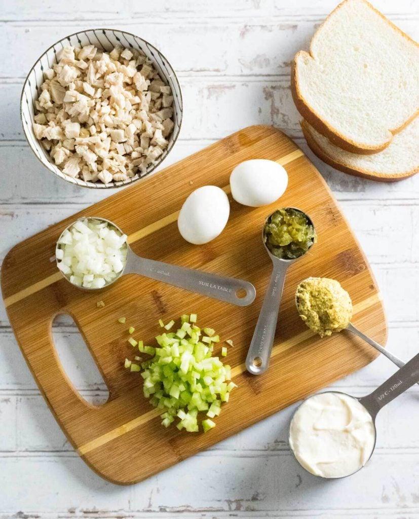 Chicken sandwich spread ingredients on cutting board.