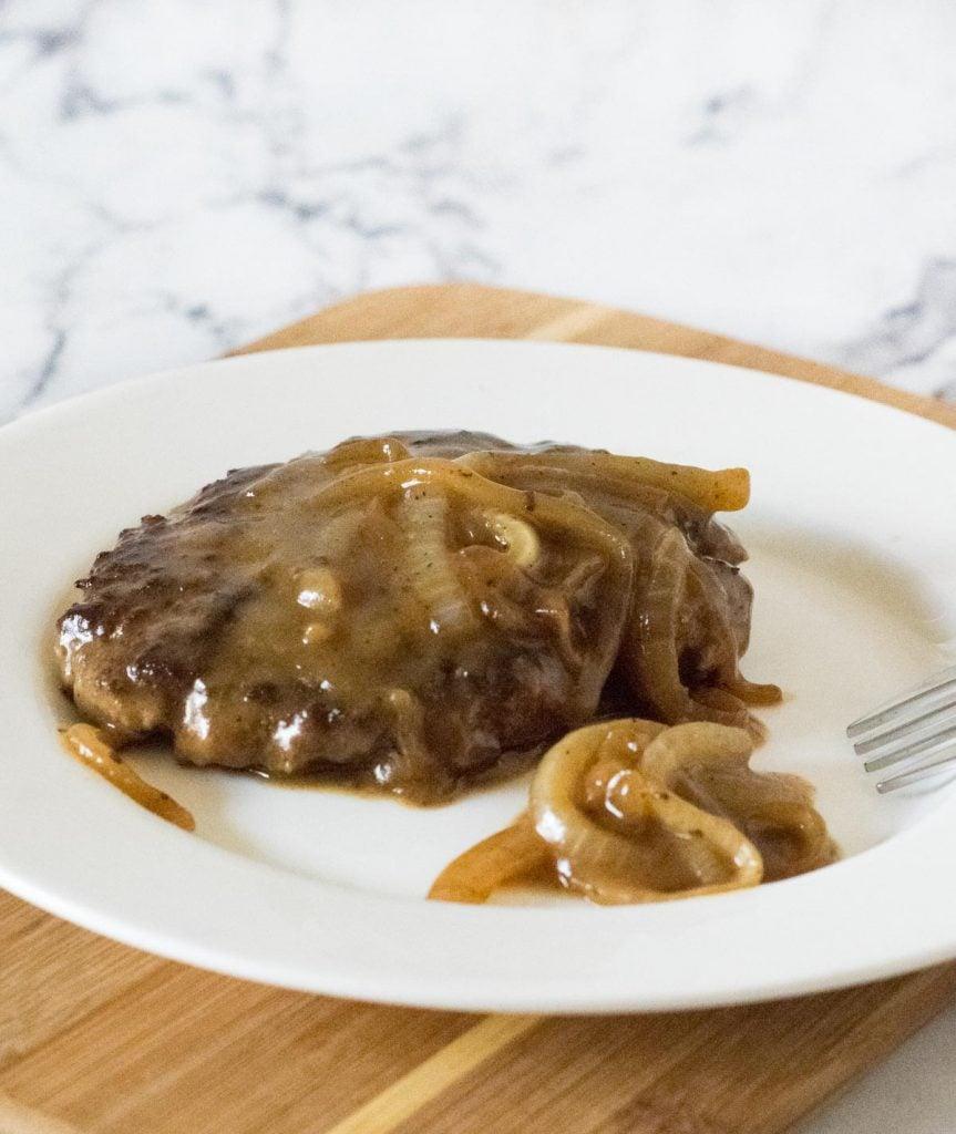 Classic Salisbury steak on white plate.