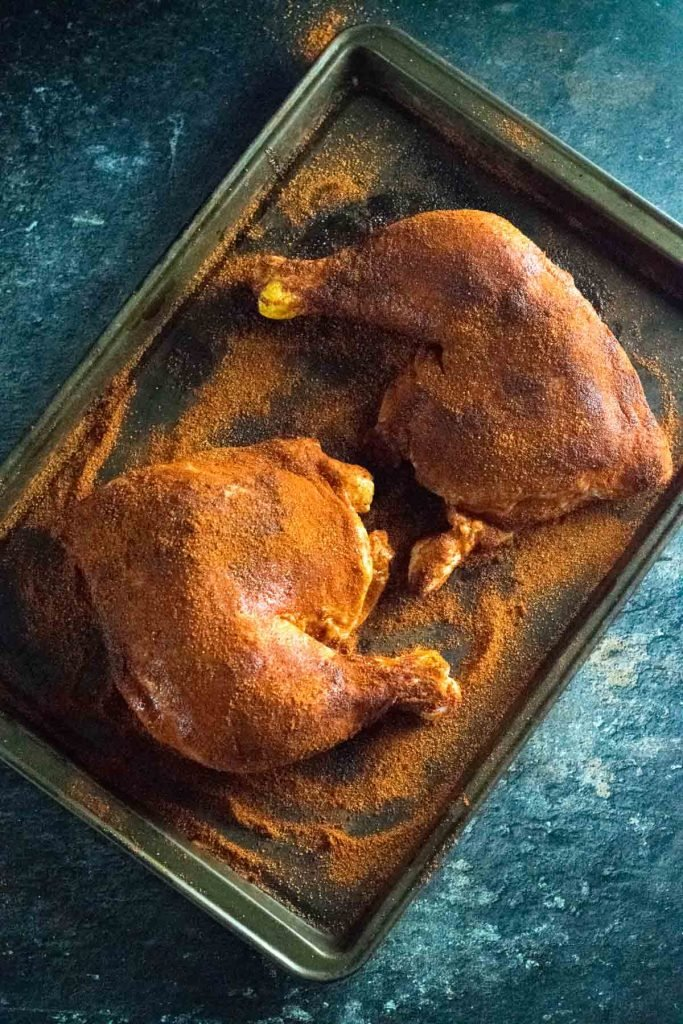 Dry rubbed chicken leg quarters.