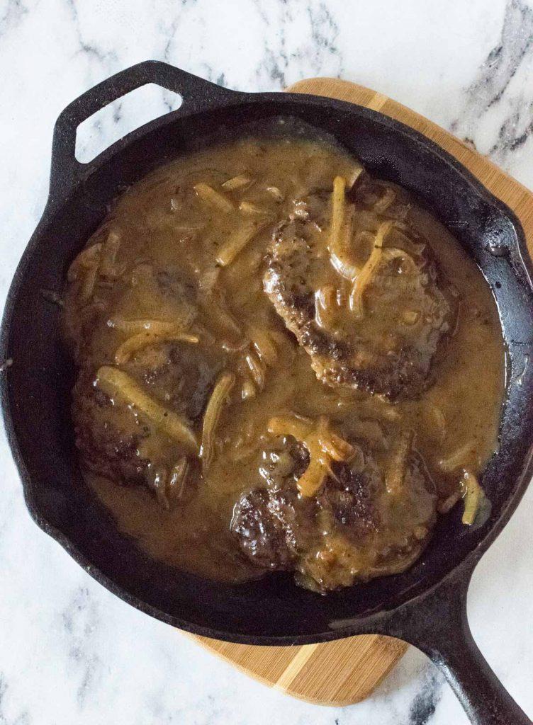 Old fashioned Salisbury steak in black skillet.