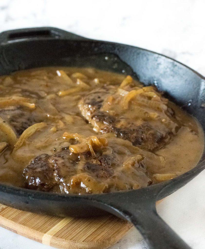 Salisbury steak in cast iron skillet.
